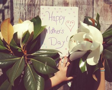 Happy Mothers Day Card with flowers and a small hand holding the card