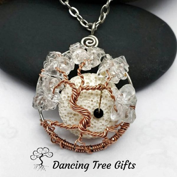 White Quartz tree of life April birthstone leaning against a black stone on a white background