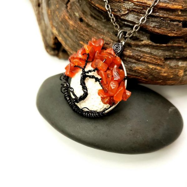 Carnelian Tree of Life Pendant with black copper wire tree sitting on a rock and wood piece with a white background