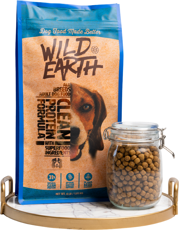 Wild earth natural dog food bag with some food in glass jar on tray with white background