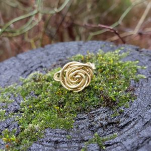 Gold Colored copper rose ring on moss covered stump
