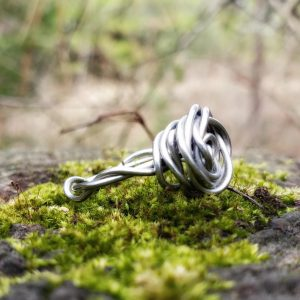silver rose ring with twisted shank on a moss covered stump